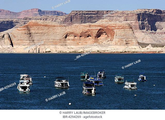 Red Navajo Sandstone cliffs at Lake Powell, houseboats in Wahweap Bay, Page, Arizona, USA