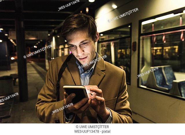 Businessman using cell phone at tram station at night
