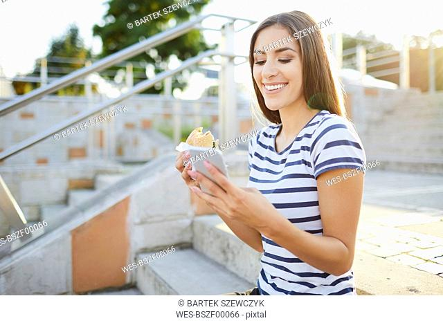 Young woman sitting on stairs eating bagel and using smartphone