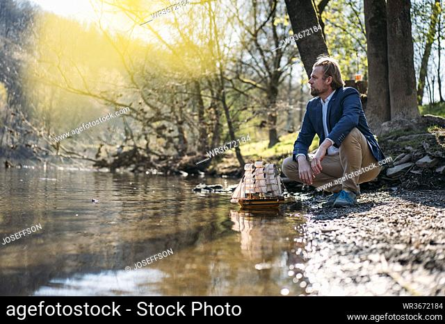 Male entrepreneur looking away while crouching by model boat at riverbank in park