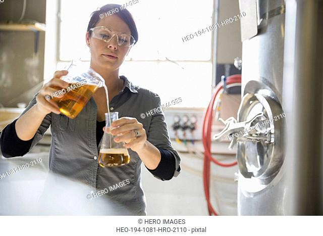 Brewery worker pouring beer from beaker into flask
