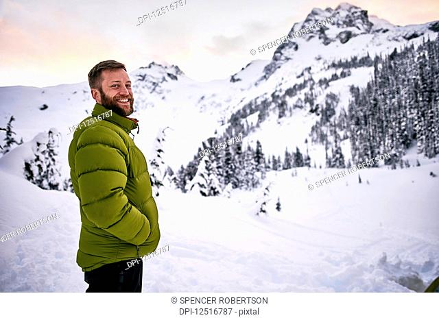 Portrait of a man standing in the snow-covered mountains at dusk; British Columbia, Canada