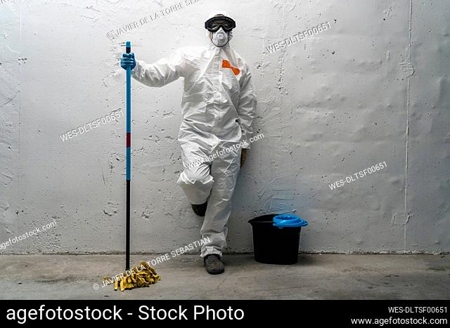 Woman with cleaning equipment, wearing protective clothing, leaning against wall