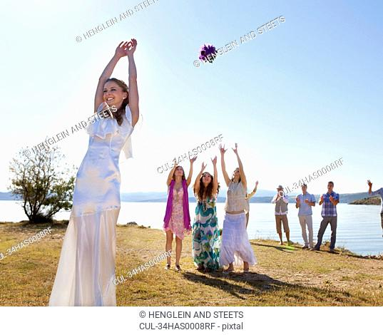 Bride throwing bouquet to friends