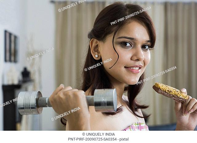 Woman holding a weight and a whole grain bar