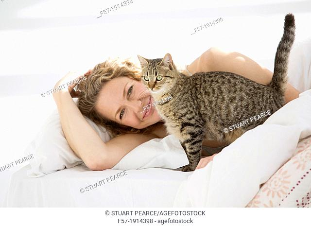 Attractive young woman in bed with her cat