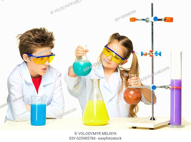 Two cute children at chemistry lesson making experiments on white background