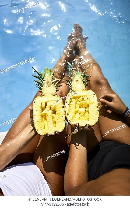 Two young women by the pool, eating pineapple. Chersonissos, Crete, Greece