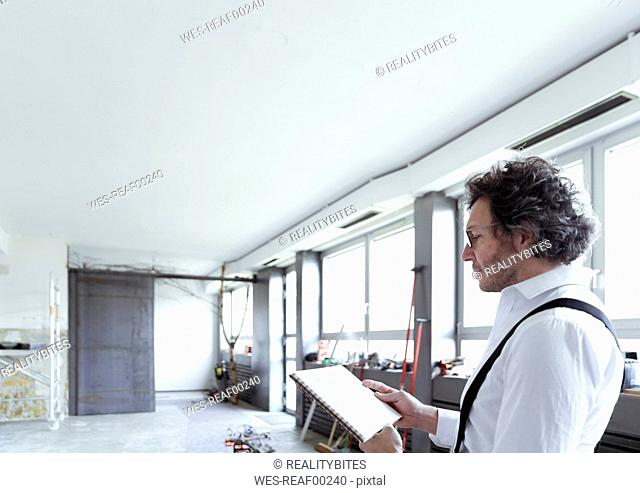 Architect with sketch book at construction site