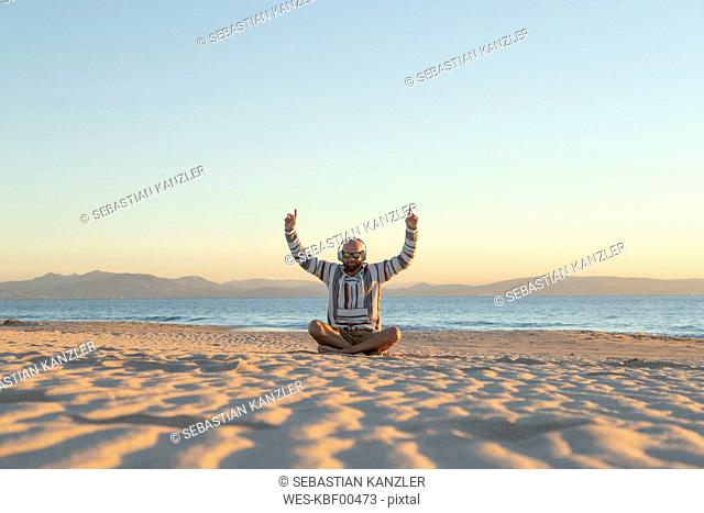 Man with headphones and sunglasses sitting on the beach