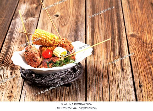 Minced meat kebabs on wooden skewers and roasted sweetcorn