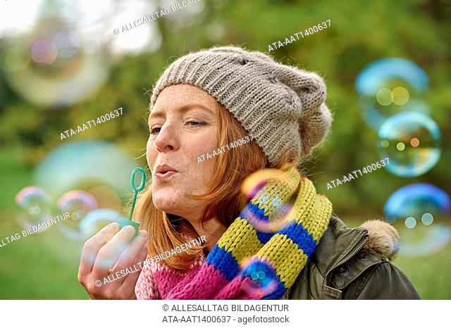Woman blowing rainbow bubbles