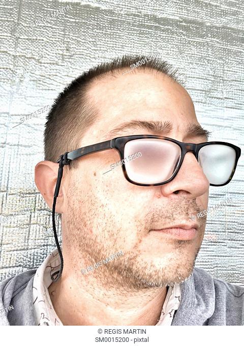 Unshaven man with fogged up prescription glasses