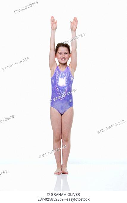Portrait of a young female gymnast taken in the studio on a white background. She is wearing a leotard and smiling at the camera