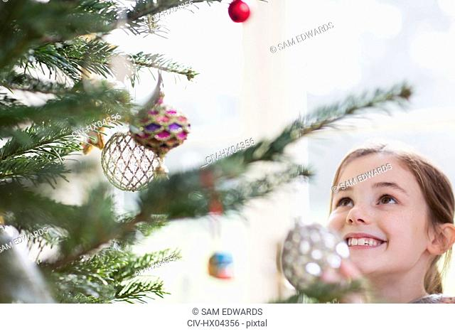 Smiling girl looking up at ornaments on Christmas tree