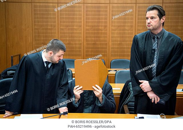 Suspected Islamist Halil D.( C) remains seated while his defenders Ali Aydin (L) and Andreas Bensch (R) rise at the entry of the court in the regional court in...