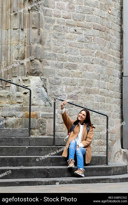 Smiling young woman sitting on stairs in the city taking a selfie, Barcelona, Spain