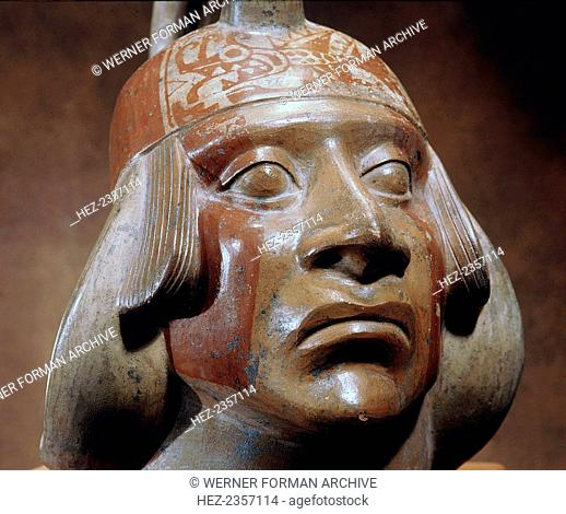 Stirrup-spouted Mochica ceramic portrait jar depicting a face of a nobleman, north coast of Peru, 100-600. The red face bands, distinctive coiffure