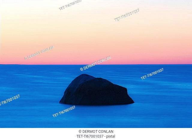 USA, Massachusetts, Cape Cod, Orleans, Rock in sea at sunset