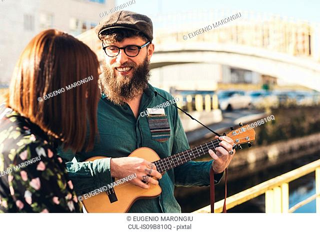 Hipster couple playing ukulele by canal