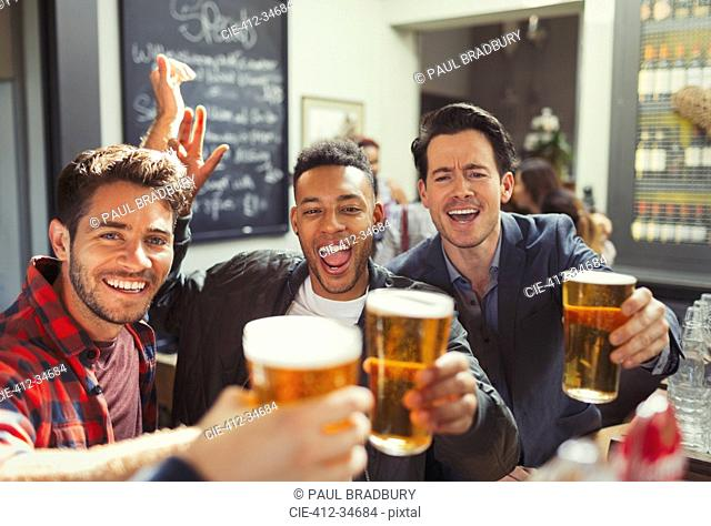 Portrait enthusiastic men friends toasting beer glasses at bar