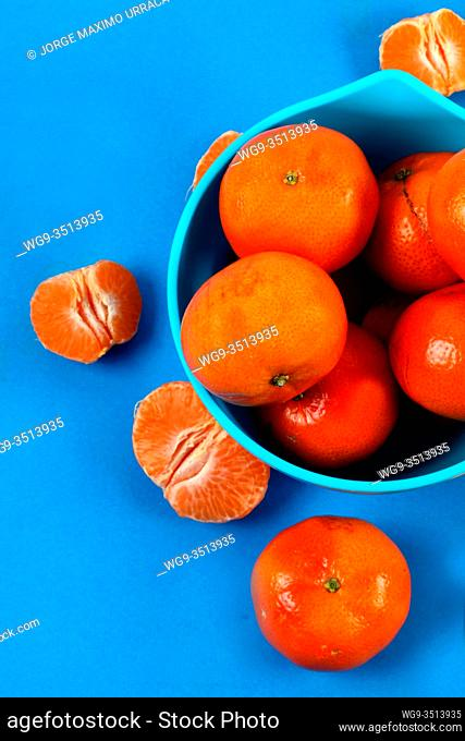 Blue bowl with tangerines in blue background