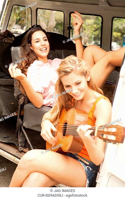 Young women with guitar on camper van, Rio De Janiero