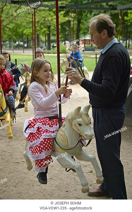 Children on carousel in park, Paris, France