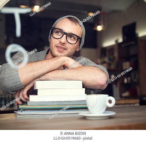 Dreaming nerdy male student in cafe. Krakow, Poland