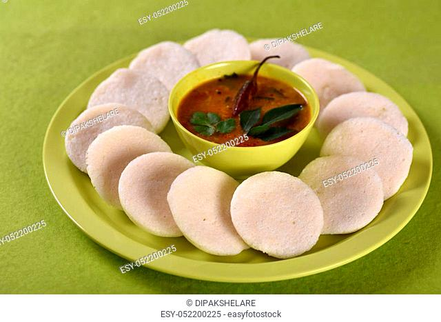 Idli with Sambar in bowl on green background, Indian Dish: south Indian favourite food rava idli or semolina idly or rava idly
