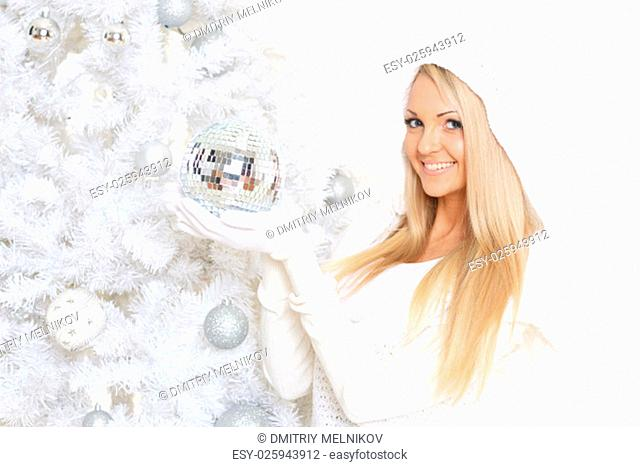 Young happy beautiful woman in winter clothes with mirror ball stands near Christmas tree on a white background