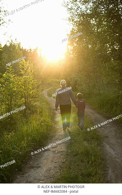 Mother and daughter walking through dirt track