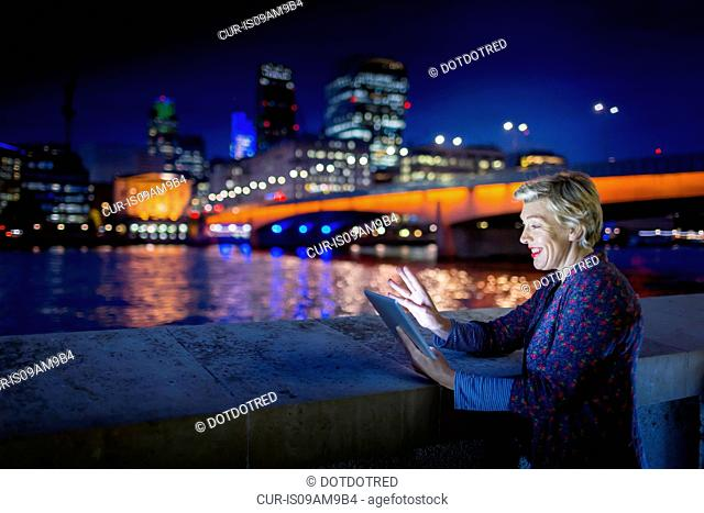 Mature businesswoman using digital tablet on Thames waterfront at night, London, UK