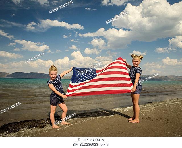 Caucasian girls holding American flag at beach