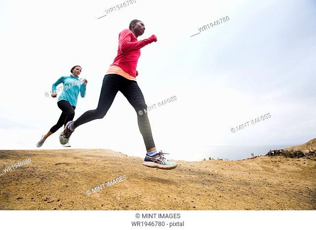 Two women jogging along the coast