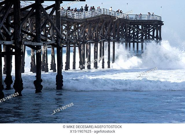 Pacific Coast waves seems to swallow a wood pier on the coast in San Diego, California