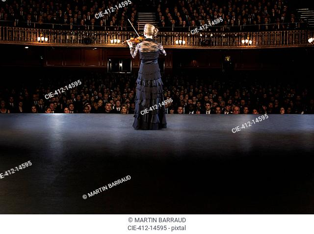 Violinist performing on stage in theater