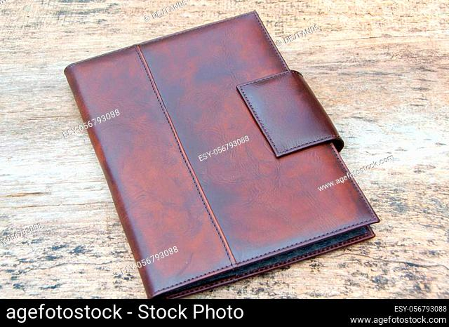 Brown leather organizer planner on the wooden backgrounde. Front and back side