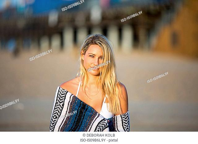 Portrait of sultry young woman wrapped in blanket on beach, Santa Monica, California, USA