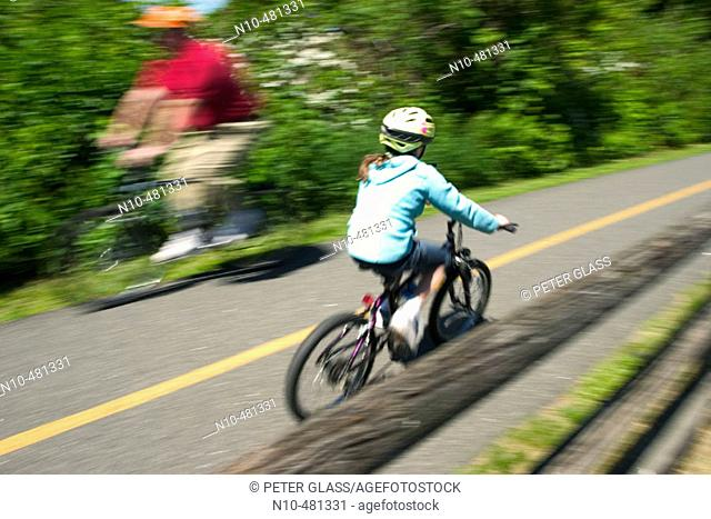 Young girl, wearing a helmet, riding a bicycle on a bike trail