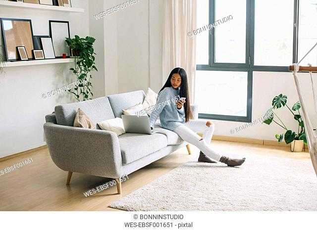 Young woman with smartphone sitting on couch at home looking at laptop