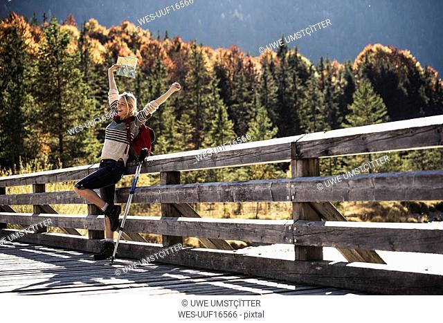 Austria, Alps, happy woman on a hiking trip with map on a bridge