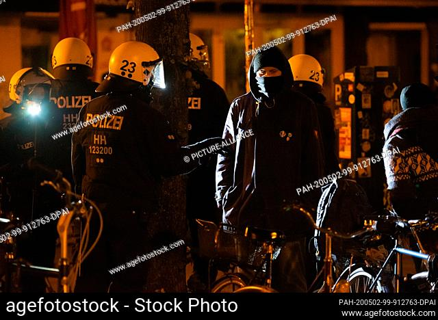 01 May 2020, Hamburg: A riot cop talking to a hooded man. Photo: Jonas Walzberg/dpa. - Hamburg/Hamburg/Germany