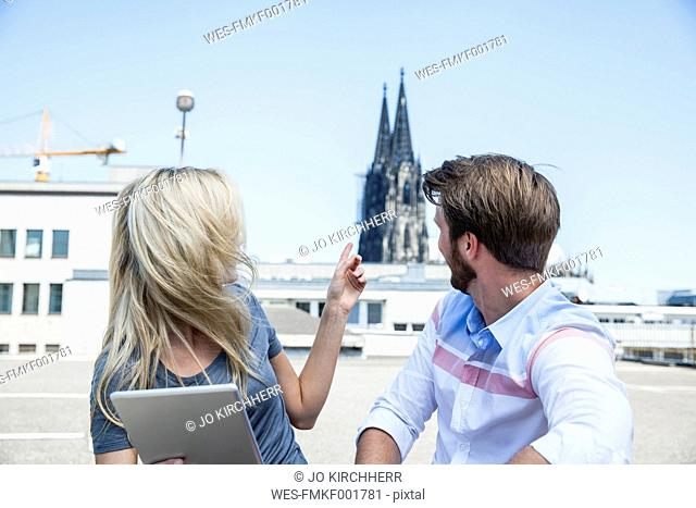 Germany, Cologne, young couple with digital tablet looking at Cologne Cathedral