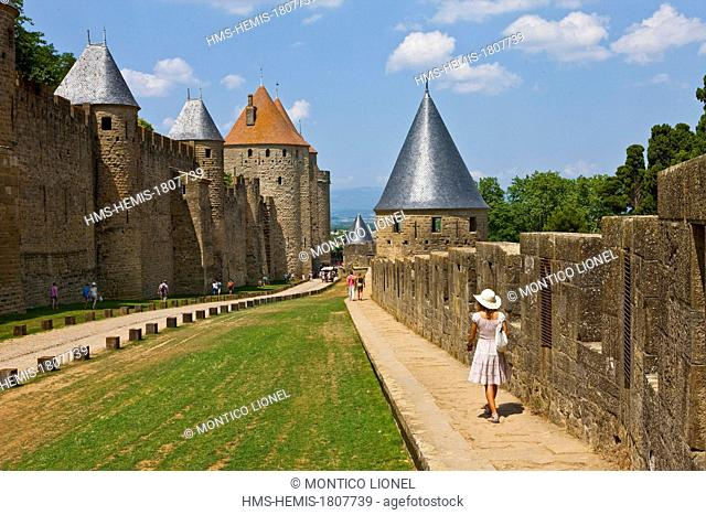 France, Aude, Carcassonne, Medieval city listed as World Heritage by UNESCO, high lices between the double walls of the city walls, woman walking