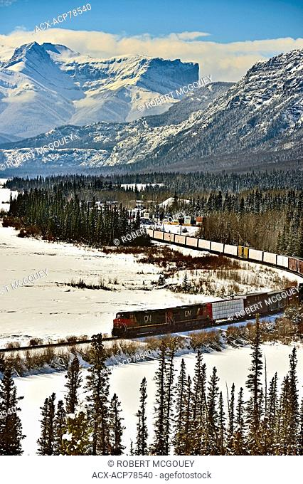 A Canadian National freight train traveling through the snow - capped rocky mountains of Alberta Canada