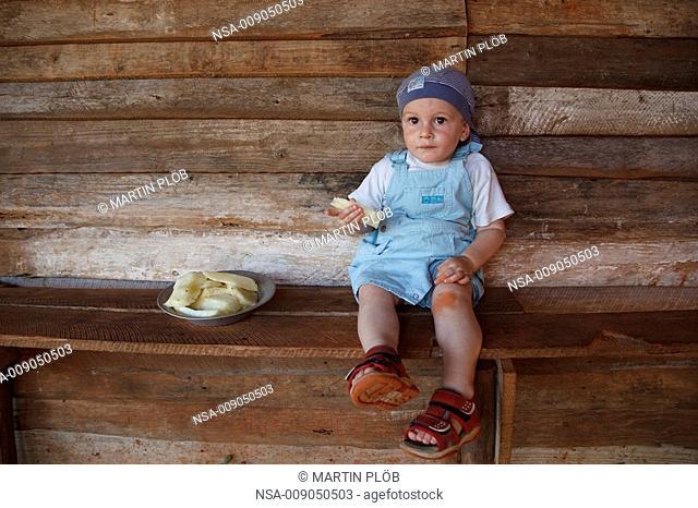 child eating pineapple