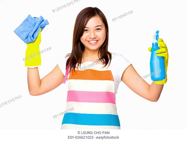 Asian housewife using the rag and bottle spray