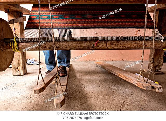 A Zapotec indigenous man uses a hand loom to weave traditional carpets October 30, 2013 in Teotitlan de Valle, Mexico