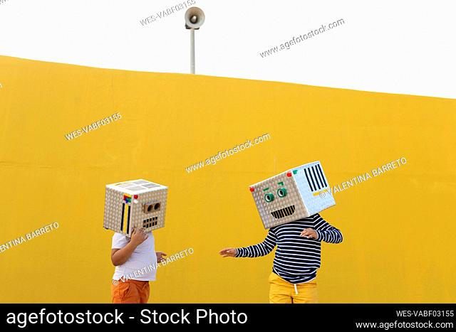 Friends wearing robot costumes standing against yellow wall